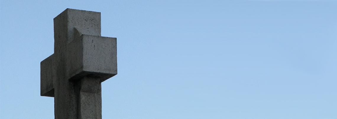 A picture of a solid stone cross in front of a clear blue sky.